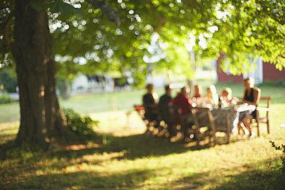 Family having meal in garden - p312m970020f by Johan Ödmann