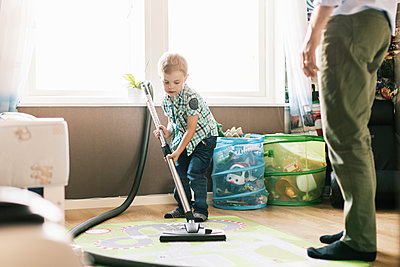 Boy vacuuming floor while father standing at home - p426m1179351 by Kentaroo Tryman