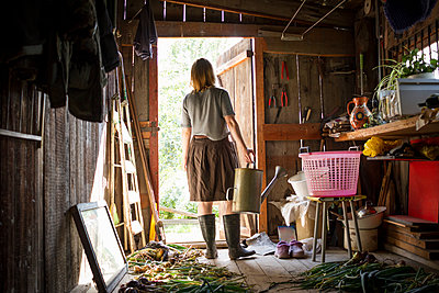 Young woman carrying watering can looking out from  garden shed - p429m1417781 by Chuvashov Maxim