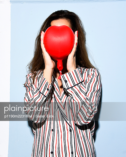 Young woman hiding face behind a red balloon - p1190m2231694 by Sarah Eick