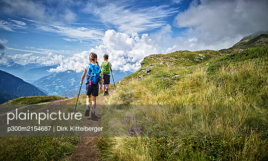 Boy and girl hiking in alpine scenery, Passeier Valley, South Tyrol, Italy - p300m2154687 by Dirk Kittelberger
