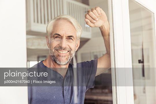 Portrait of smiling mature man looking out of window - p300m2167040 by Floco Images