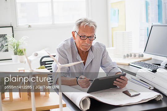 Older Caucasian architect using digital tablet in office - p555m1412285 by JGI/Tom Grill
