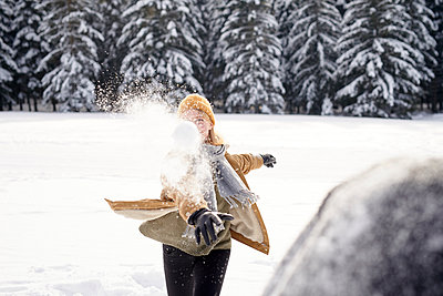 Young couple having a snowball fight - p1124m1589321 by Willing-Holtz