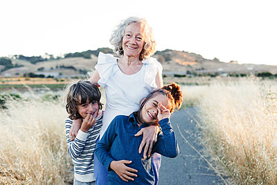 Portrait of happy grandmother with grandsons on country road - p1166m1489574 by Cavan Images