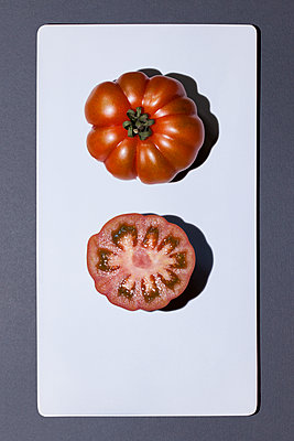 Whole and sliced oxheart tomato on white board - p300m1121176 by Monika Nesslauer