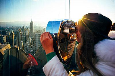 Woman on Top on the Rock looking through binoculars, New York City, United States - p300m2155676 von Oscar Carrascosa Martinez