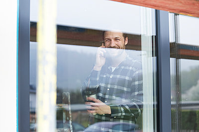 Construction worker talking over smart phone in house seen through window - p300m2214123 by MiJo