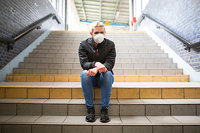 Teenage girl wearing protective mask and gloves sitting on stairs of train station - p300m2225047 by Anke Scheibe