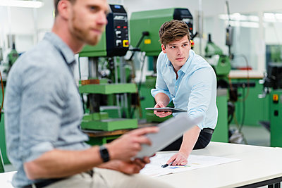 Male engineer holding digital tablet with entrepreneur looking away while having meeting in factory - p300m2242242 by Daniel Ingold