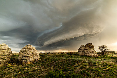 Storm clouds over rock formations in field, Lamar, Colorado, United States, North America - p429m1519563 by Jessica Moore