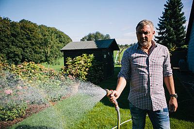 Mann mit grauen Haaren wässert den Garten - p586m983659 von Kniel Synnatzschke
