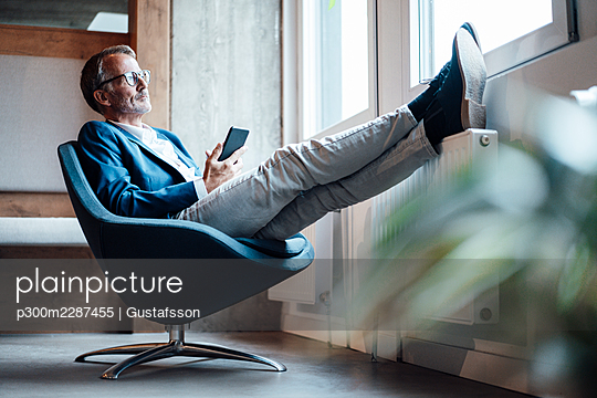 Businessman holding mobile phone while sitting on chair in office - p300m2287455 by Gustafsson