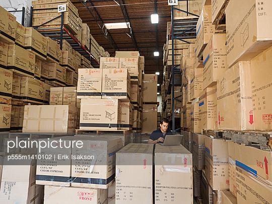 Caucasian worker using laptop in warehouse - p555m1410102 by Erik Isakson