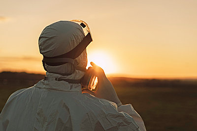 Rear viewof man wearing protective suit and mask in the countryside at sunset - p300m2166408 by Eloisa Ramos