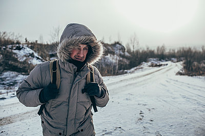 Hiker carrying backpack while standing on snow covered landscape - p301m1130864f by Vasily Pindyurin
