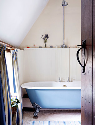 View through doorway to room with freestanding roll top bath - p349m790318 by Brent Darby