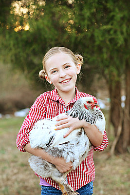 Caucasian girl holding chicken on farm - p555m1408734 by Shestock
