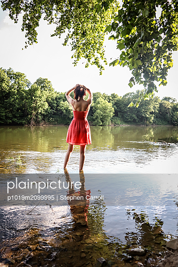 Woman standing in river - p1019m2099995 by Stephen Carroll