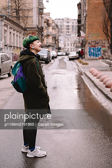 Happy non-binary female hipster standing on the road in city - p1166m2191865 by Cavan Images