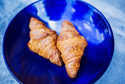 High angle close up of two freshly baked croissants on a blue plate. - p1100m1530967 by Mint Images