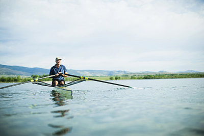A man in a rowing boat using the oars. - p1100m876295f by Jamie Kripke