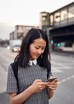 Asiatin mit Smartphone in der Stadt - p1124m1169914 von Willing-Holtz