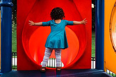 Little girl at top of slide - p1166m2073852 by Cavan Images