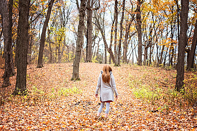 Young Red Hair Girl Playing Outside in Fall Leaves - p1166m2147068 by Cavan Images