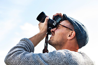 Low angle view of man photographing sky through digital camera - p1185m1015868f by Astrakan