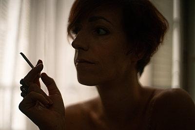 Woman smoking a cigarette - p1321m2053953 by Gordon Spooner