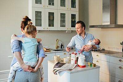 Family in kitchen - p312m1557149 by Anna Rostrom