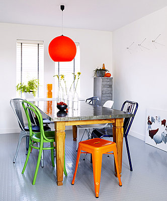 Bright pendant light above stainless steel topped table with mismatched chairs in Newcastle dining room - p349m790325 by Brent Darby