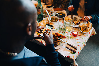 High angle view of young man photographing food in plate while sitting at restaurant during dinner party - p426m2046346 by Maskot