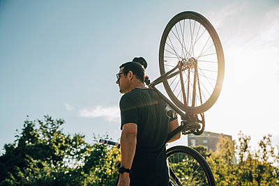 Male athlete carrying bicycle on shoulder against sky on sunny day - p426m2270613 by Maskot