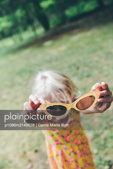 Little girl holding sunglasses - p1086m2149638 by Carrie Marie Burr