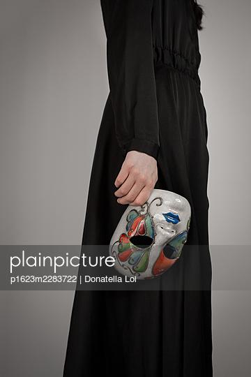 Girl holding mask - p1623m2283722 by Donatella Loi