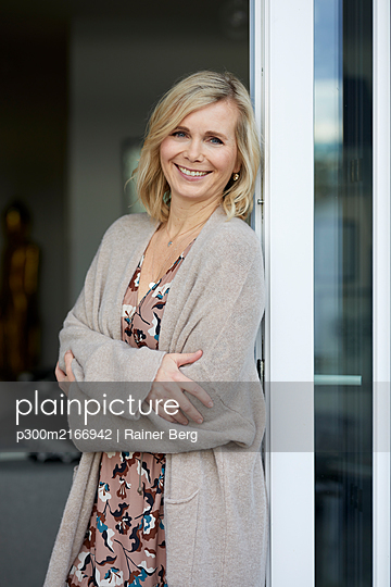 Portait of smiling blond woman leaning against balcony door at home - p300m2166942 by Rainer Berg