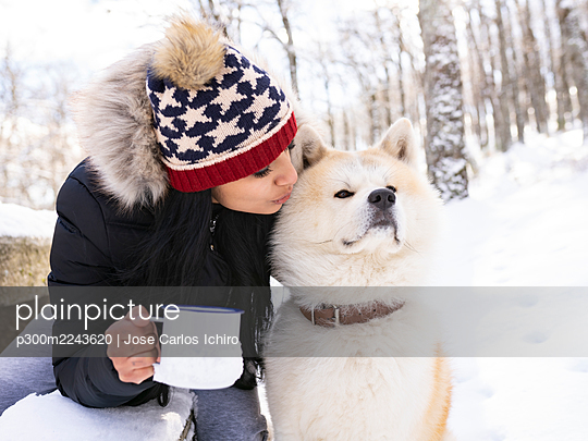 Mid adult woman with coffee cup kissing dog while sitting on bench in snow - p300m2243620 by Jose Carlos Ichiro