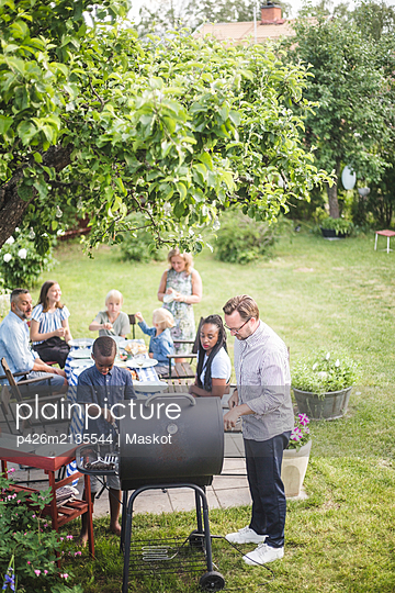 High angle view of man preparing barbecue grill with boy while family and friends sitting at table in backyard - p426m2135544 by Maskot