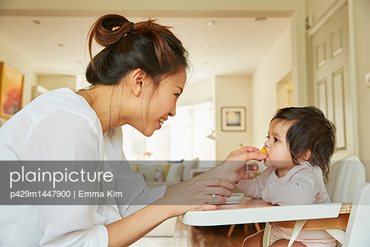 Woman feeding baby daughter in high chair - p429m1447900 by Emma Kim
