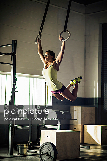Young woman training on rings in gymnasium - p429m884235 by Corey Jenkins