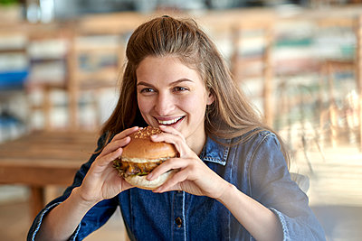 Young woman eating hamburger - p1124m1564725 by Willing-Holtz