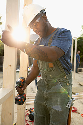 Man using power drill, working at construction site - p1192m2024535 by Hero Images