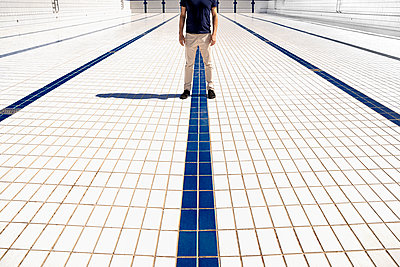 Man stands on tiles in empty pool - p1625m2263146 by Dr. med.