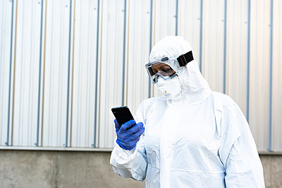 Female scientist wearing protective suit and mask and looking at smartphone - p300m2170998 by Eloisa Ramos