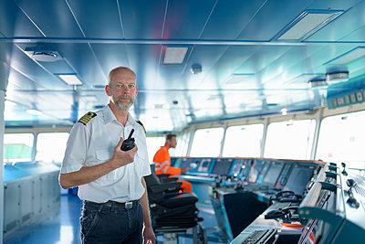 Portrait of ship's captain on bridge onboard ship in port - p429m2019468 by Monty Rakusen