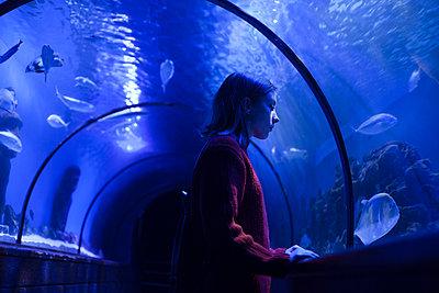 Caucasian woman admiring fish in aquarium - p555m1504156 by Dmitriy Bilous