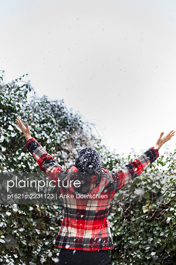 Woman with checked jacket and outstretched arms in the snow - p1621m2231123 by Anke Doerschlen