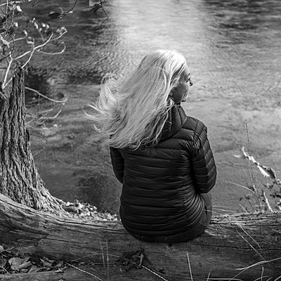 Woman sitting on log by river in Boise, Idaho, USA - p1427m2146773 by Steve Smith